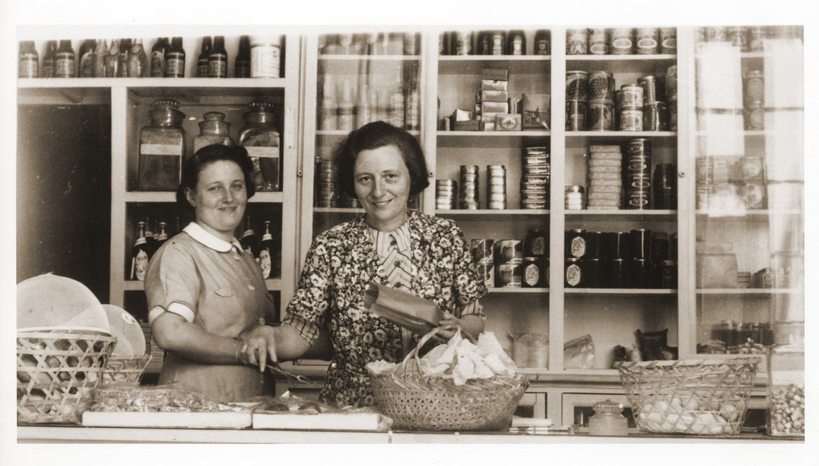 Two German Jewish refugee women stand behind the counter of the Elite Provision Store (delicatessen) in Shanghai.