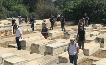 """Participants take part in """"Remote X"""" in a Jerusalem cemetery. The tour is based on a skeleton of a narrative in which the performers are """"remoted"""" from the normal ways they interact with the city, experiencing it as a meta-reflection while walking the streets. Credit: Eliana Rudee."""