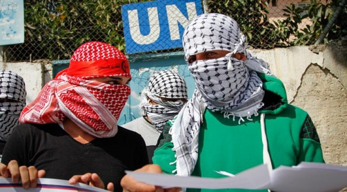 Masked Palestinians demonstrate in front of the headquarters of the Agency for Refugees in Balata refugee camp in protest against the policy of Scott Anderson, director of UNRWA in the West Bank, on Sept. 17, 2017. Photo by Nasser Ishtayeh/Flash90.