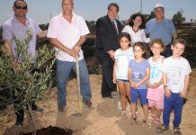 From left: Ron Werner, Mayor Gadi Yarkoni, CEO of Jewish National Fund-USA Russell Robinson, Michal Uziyahu, Alon Shuster and kids in Eshkol plant an olive tree in the burnt ground where an incendiary kite from Gaza had destroyed all vegetation. Credit: Courtesy.