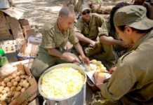 """IDF reserve soldiers seen making food in a staging area near the border with Gaza in southern Israel on July 20, 2014, during Israel's """"Operation Protective Edge."""" Photo by Moshe Shai/Flash90"""