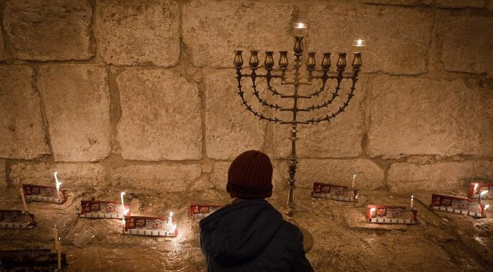 "Candles on the first night of the Jewish holiday of Hanukkah, in the Jerusalem neighborhood of Mea Shearim. Hanukkah, also known as the ""Festival of Lights,"" is an eight-day Jewish holiday commemorating the rededication of the Holy Temple. The festival is observed by the kindling of the lights of a ""hanukkiyah,"" a nine-branched candelabrum with one additional light being lit on each night of the holiday. Dec. 24, 2016. Photo by Sebi Berens/Flash90."