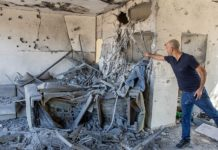 A man stands inside a house that was hit by a rocket fired from the Gaza Strip in the southern Israeli city of Ashkelon on Nov. 13, 2018. Photo by Nati Shohat/Flash90.