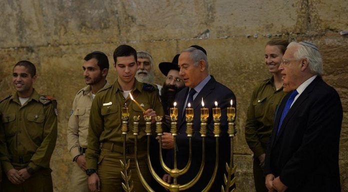 Israeli Prime Minister Benjamin Netanyahu lights the Hannukah menorah at the Western Wall in Jerusalem on Dec. 6, 2018, with U.S. Ambassador to Israel David Friedman watching. Credit: Kobi Gideon/GPO.