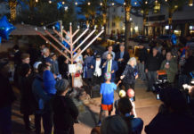 Rabbi Polichenco, with microphone, explains the significance of Chanukah as Nancy Harrison gives a hand-held light to a youngster